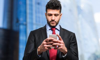 Businessman typing sms on his smartphone
