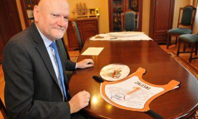 Prezydent Michał Zaleski przekazuje plastron na aukcję (fot. torun.pl)